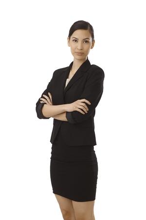 mini falda: Atractiva empresaria de pie brazos jóvenes cruzaron, sonriendo.