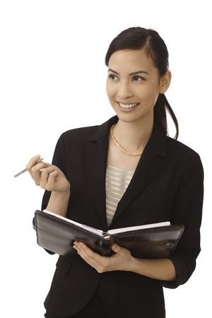 secretaria: Secretaria joven feliz que hace notas de organizador personal, sonriendo, mirando a otro lado.
