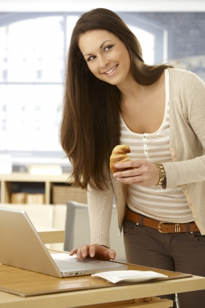 surfing the internet: Happy young woman standing by table, using laptop computer, having breakfast croissant, looking away.