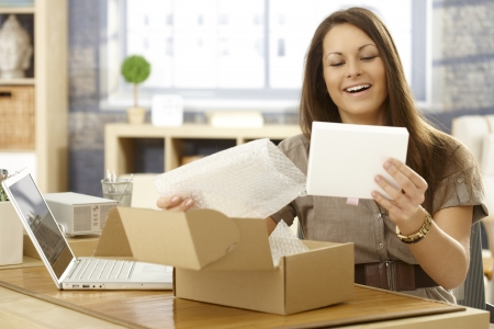 unpacking: Young woman unpacking postal packet, smiling happy. Stock Photo