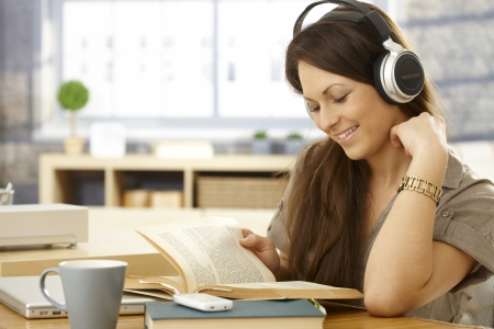 music education: Young woman reading a book, using headphones, smiling.