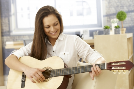girl playing guitar: Happy girl playing guitar at home in living room, smiling.