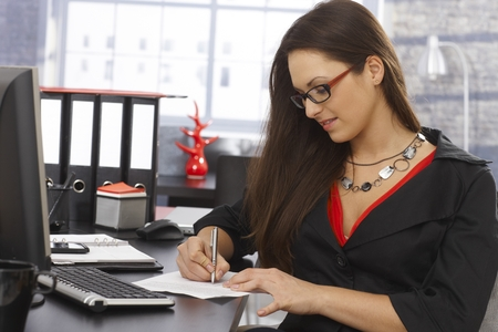 taking notes: Young secretary sitting at desk in office, writing notes.