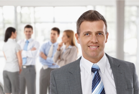 Middle-aged businessman in front, business team talking in background. Imagens