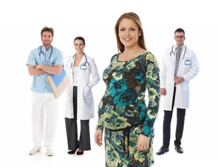 Portrait of happy young pregnant woman with medical team in background, isolated on white background. photo