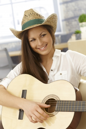 Portrait of happy young female guitar player with instrument. photo
