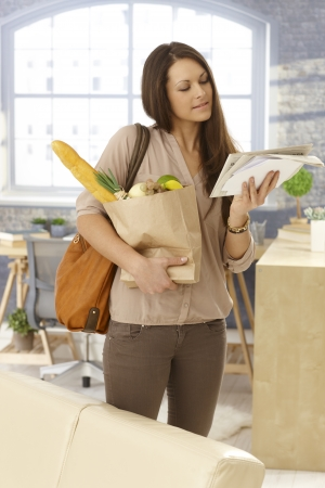 arriving: Young woman arriving at home, checking mail, holding shopping bag. Stock Photo