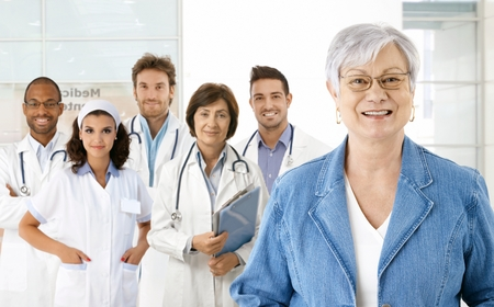 Happy senior woman with medical team in background. Stock Photo - 23413727
