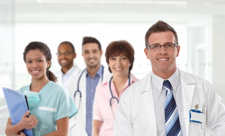 Portrait of mid-adult caucasian male doctor with medical team in background. Stock Photo - 23413726