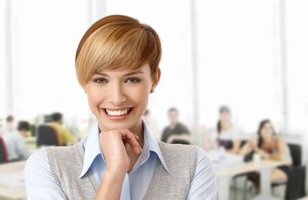 gingerish: Happy young woman at office smiling. Stock Photo