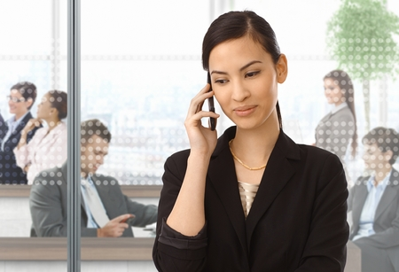 Asian businesswoman using mobile phone at office, smiling. photo