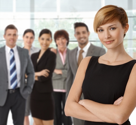 Beautiful young businesswoman smiling with business team in background.