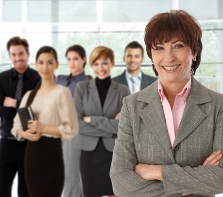 Portrait of happy senior businesswoman and her business team. Stock Photo