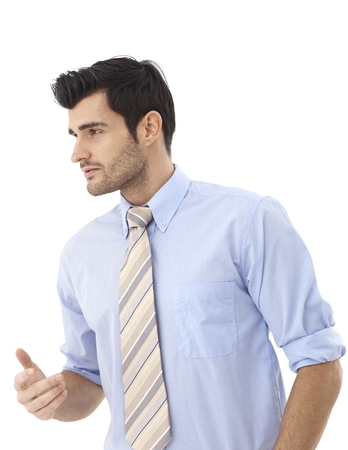 Young businessman turning right, gesturing over white background. photo