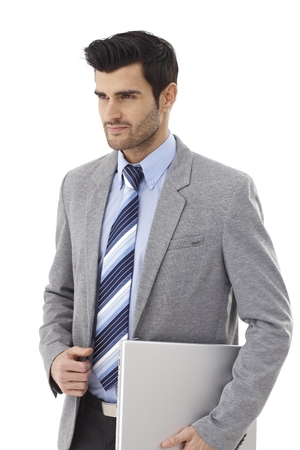 Handsome young businessman walking with laptop computer in hand, looking away. photo