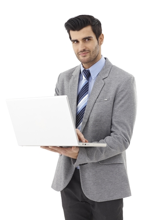Young businessman holding laptop computer, looking away, standing. photo