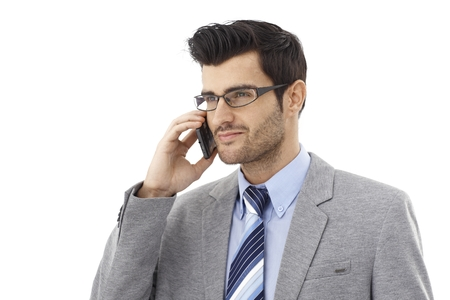 smiing: Handsome young businessman talking on mobilephone, smiing.