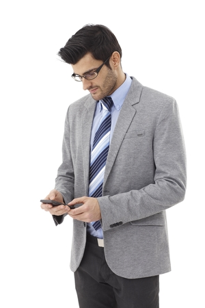 Young businessman using mobilephone, dialing. photo