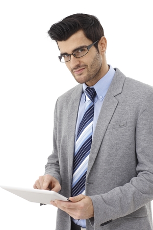 Handsome young businessman using tablet pc, looking at camera, wearing glasses. photo