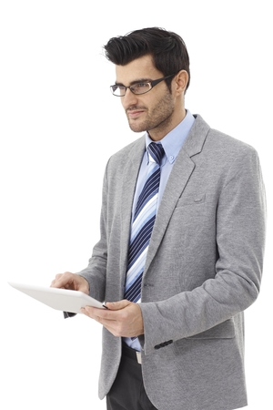 Young businessman using tablet computer, looking away, smiling. photo
