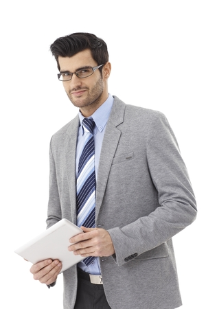 Happy businessman using tablet computer, smiling, looking at camera. photo