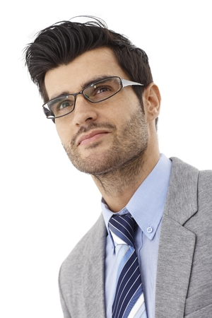 Closeup portrait of handsome young bristly businessman in glasses, looking up. Photographed from below. photo