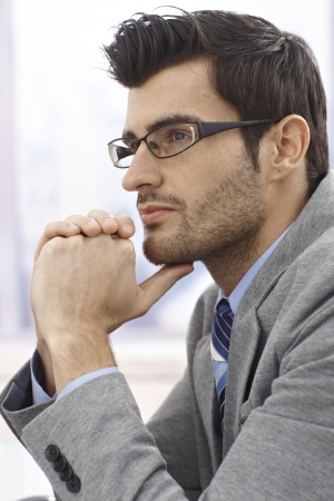 Closeup profile of thinking businessman in glasses. photo