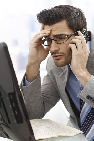 Businessman looking desperate while talking on mobile and checking computer. photo