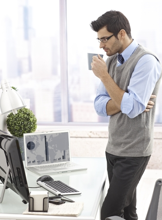 Businessman standing by desk, drinking coffee, looking at computer screen. photo