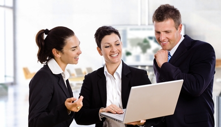 Happy business people with laptop working together laughing. Stock Photo - 23732823