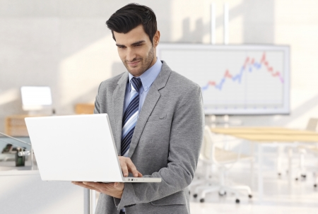Businessman working with laptop in meeting room, smiling.