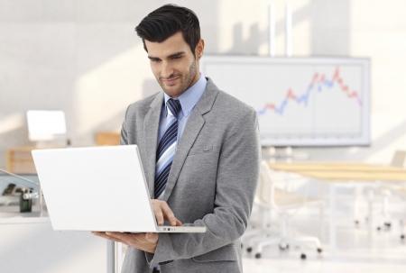 Zakenman werken met de laptop in de vergaderzaal, glimlachend. Stockfoto - 23802050