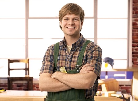 Happy young handyman carpenter in workshop, smiling. Stock Photo - 23732830