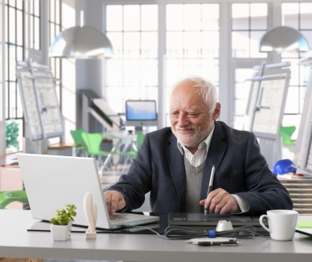 Senior engineer sitting at desk doing design work with computer at architect studio.