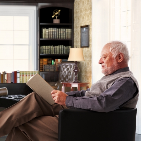 Elderly man sitting in armchair reading book at study at home. photo