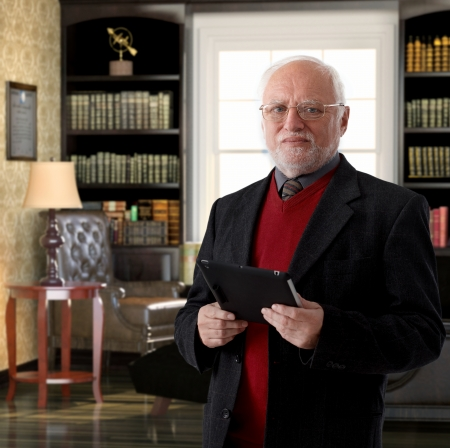 professor: Portrait of elderly professor at study holding tablet computer Stock Photo