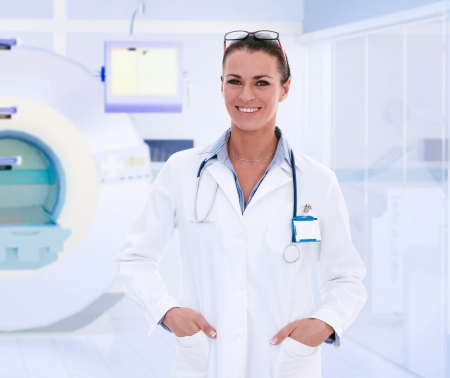 Happy middle-aged caucasian female doctor in MRI room at hospital. Imagens