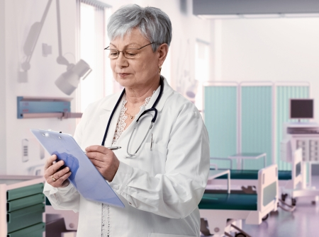 Old female doctor writing notes on clipboard at hospital room, photo