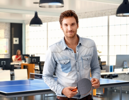 Casual man holding ping-pong racket at trendy office, smiling. photo