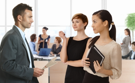 Businesspeople talking in busy office, diverse group of people. Stock Photo - 23964986