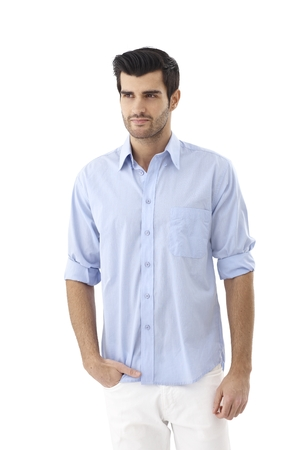 businessman standing: Casual young man standing hand in pocket, looking away.