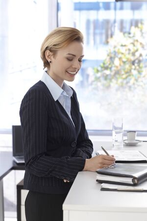 Businesswoman working, writing notes, smiling. photo