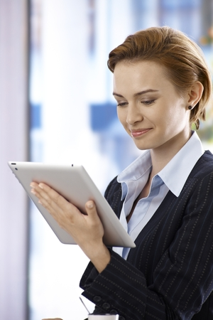 gingerish: Attractive businesswoman using tablet computer, smiling, concentrating.