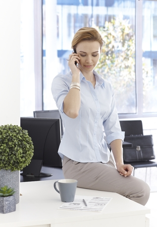 gingerish: Young businesswoman sitting on top of desk, talking on mobilephone, looking at business diagrams.