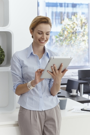 Happy young businesswoman using tablet computer, smiling. photo