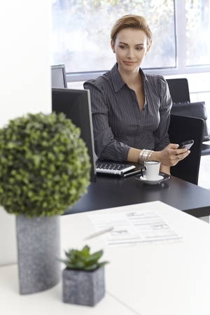 Portrait of young businesswoman sitting at desk using mobilephone, looking away, smiling. photo