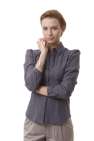 gingerish: Portrait of attractive young businesswoman looking at camera, hand on chin.