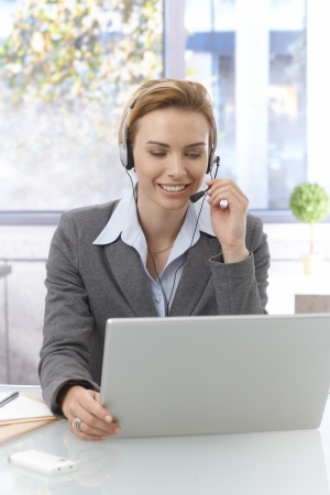 Portrait of pretty young dispatcher working , using laptop computer, wearing headphones, smiling. photo