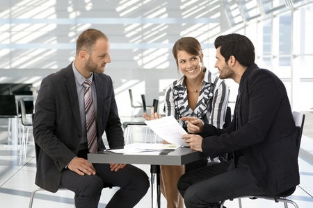 Happy corporate business people having discussion by coffee table.