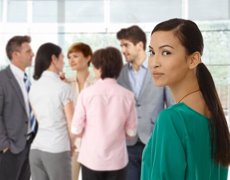 asian american: Young asian businesswoman looking back business team. Stock Photo